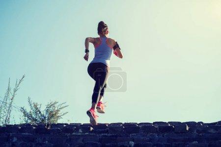 junge Fitness-Trail-Läuferin rennt auf die Spitze der großen Mauer am Berg
