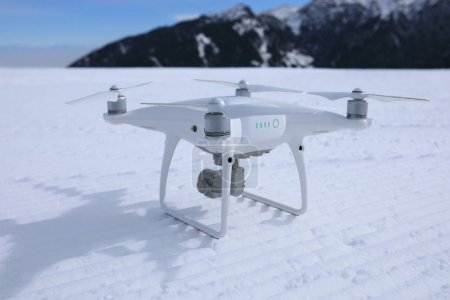 drone ready to take off at ski piste on winter mountain top