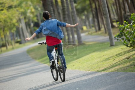 Photo for Happy woman cyclist riding bike in spring tropical park - Royalty Free Image