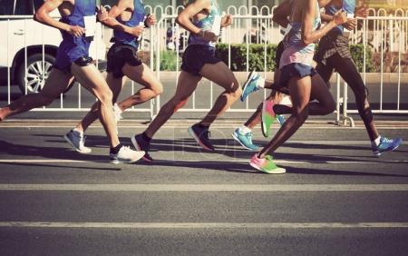 Photo pour Jambes de coureurs de marathon en cours d'exécution sur la route de la ville - image libre de droit