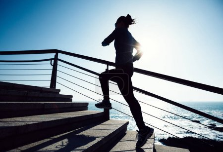 Photo for Sporty female runner running upstairs on coast trail - Royalty Free Image