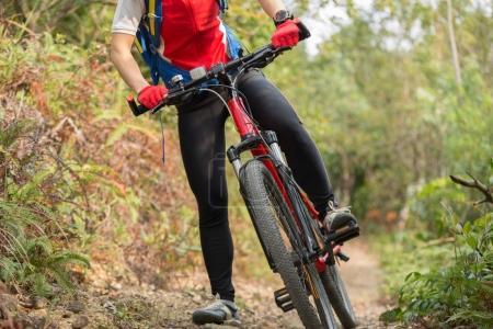 Foto de Piernas de la mujer ciclista en bicicleta de montaña en pista al aire libre en el bosque - Imagen libre de derechos