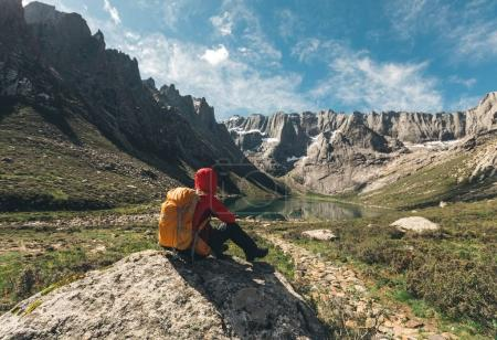 woman hiker sitting on high altitude mountain rock enjoy the view