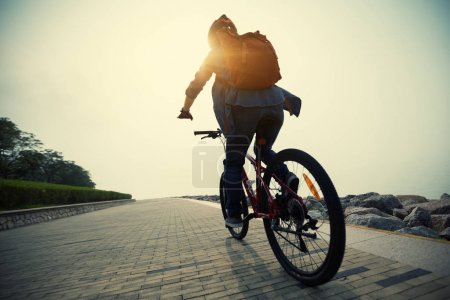 cyclist riding mountain bike in the sunrise coast