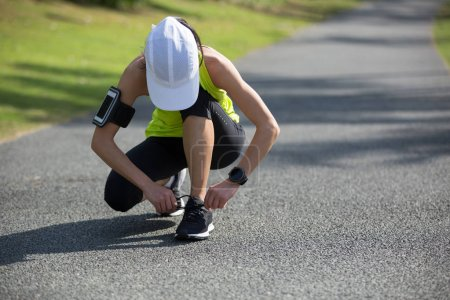 sporty young fitness woman runner tying shoelace at tropical park