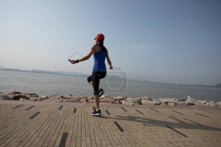 sporty young fitness woman jumping rope on coast