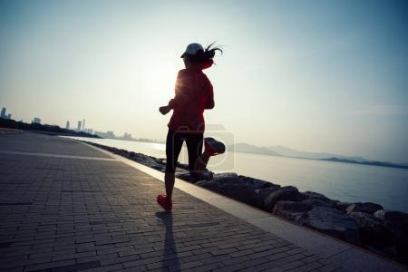 sporty young fitness woman running on sunrise seaside