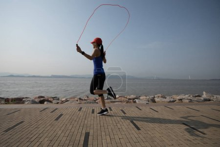 young fitness sportswoman jumping rope on coast