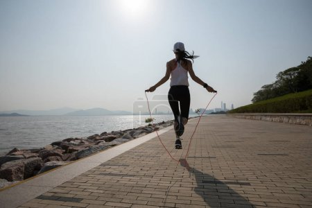 Photo for Sporty young fitness woman jumping rope on coast trail - Royalty Free Image