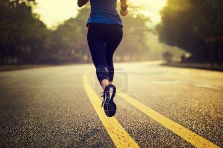 Fitness sportswoman running on trail, rear view