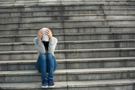 Upset woman sitting alone in city stairs