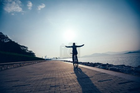 Photo for Silhouette cyclist riding bike in the sunrise coast road - Royalty Free Image