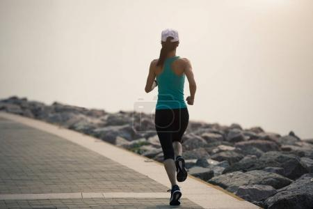 sporty young fitness woman running on coast trail