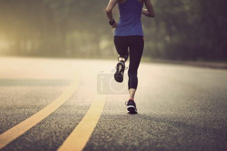 Fitness sportswoman running on sunrise trail