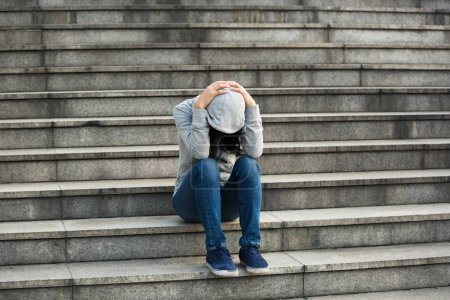 Upset woman sitting alone on city stairs