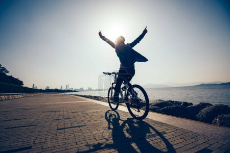 Photo for Silhouette of happy cyclist riding bike in the sunrise coast - Royalty Free Image
