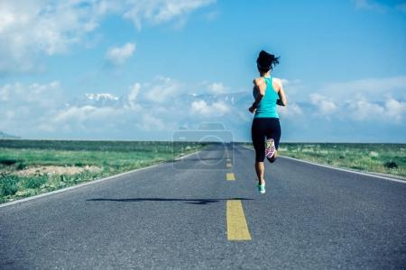 Young fitness healthy lifestyle woman runner running on wide road