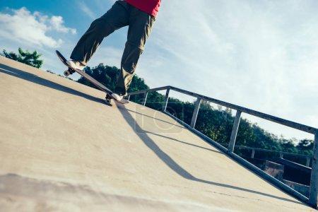 Skateboarder legs riding skateboard on skatepark ramp