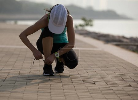 Photo for Athlete girl tying shoelaces before jogging - Royalty Free Image