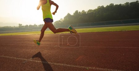 Fitness sportswoman running on sunrise track