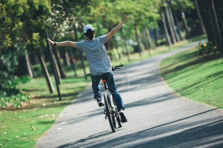 Photo for Happy woman cyclist riding bike in tropical park - Royalty Free Image