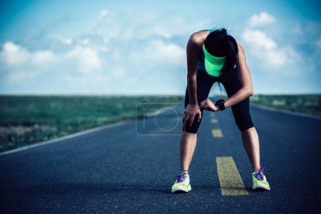 Tired woman runner checking sportswatch while resting on road