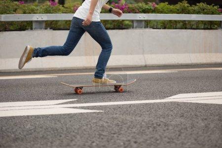 Cropped image of skateboarder sakteboarding on highway