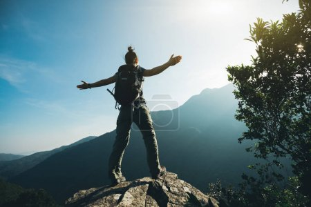Photo for Successful hiker with arms outstretched on sunrise mountain top - Royalty Free Image