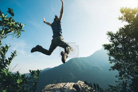 Photo for Successful hiker jumping on sunrise mountain top - Royalty Free Image
