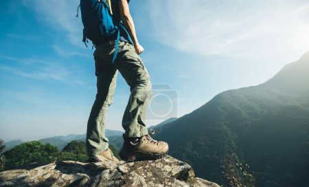 successful hiker standing on sunrise mountain top cliff edge
