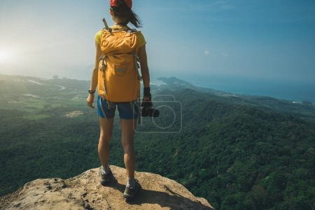 Photo pour Femme randonnée réussie debout sur le sommet de la montagne falaise bord - image libre de droit
