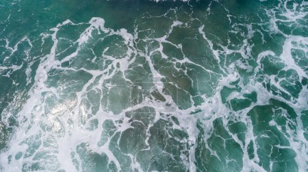 Aerial view of sea surface with splashing wave