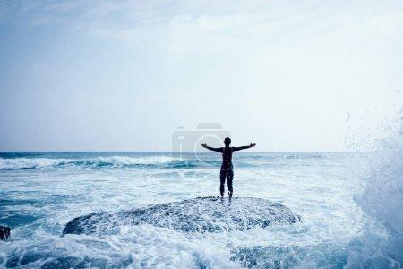 Photo pour Femme face aux vagues de mer géantes à venir avec les bras tendus - image libre de droit