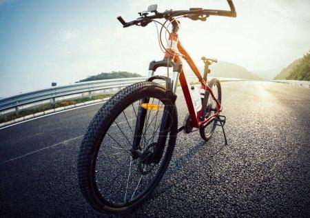 Photo pour Vélo pour l'équitation sur l'autoroute du lever du soleil - image libre de droit