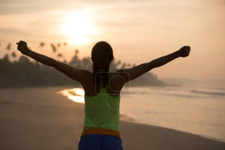 Photo pour Cheering jeune femme à bras ouverts sur la plage du lever du soleil - image libre de droit