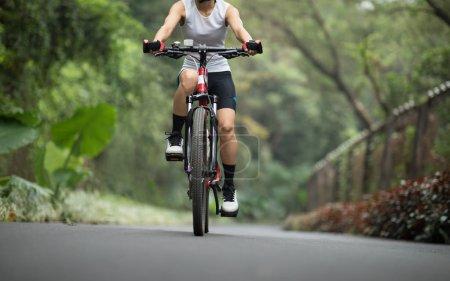 Photo pour Femme cycliste équitation VTT sur la route du parc - image libre de droit
