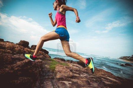 Jeune coureur de sentier de remise en forme courant jusqu'au sommet rocheux sur le bord de mer