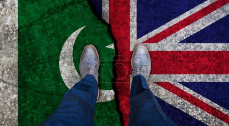 Business man stands on cracked flag of UK and Pakistan. Political concept