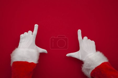 Photo for Santa Claus making frame with hand on red background with copy space - Royalty Free Image