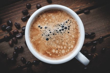 Photo for Fresh cup of coffee on a dark brown wooden table with coffee beans - Royalty Free Image
