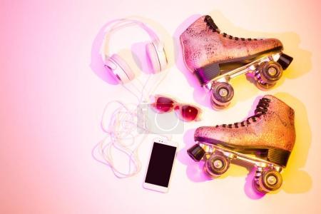 Retro pink glittery roller skates, mobile phone (s...
