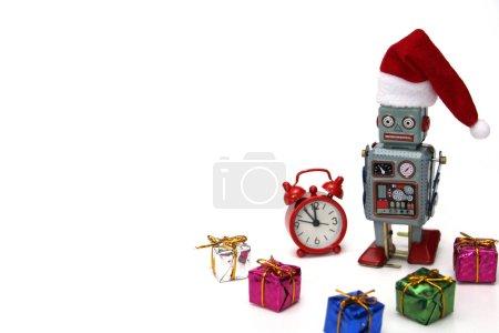 Photo pour Retro robot dans un chapeau de Nouvel An est prêt à rencontrer Noël et Nouvel An. À côté du robot se trouvent une horloge rouge, qui est presque minuit, et de nombreux cadeaux. Concept - Robot souhaite une bonne année. - image libre de droit