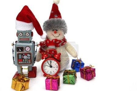Photo pour Robot rétro et bonhomme de neige prêt à faire face à Noël et au Nouvel An. À proximité se trouvent une horloge rouge, qui est presque minuit, et de nombreux cadeaux. Concept - moderne joyeux Nouvel An. - image libre de droit