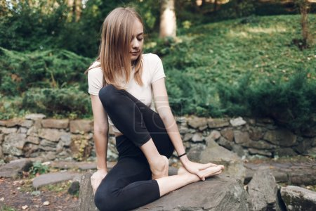 Young girl after intense jogging sits on a stone r...