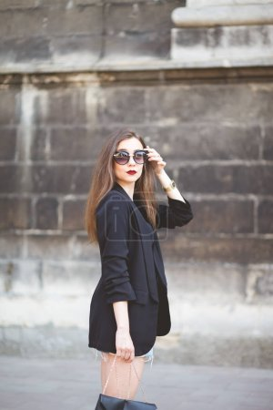 Photo for Elegant girl in sunglasses walks around the city - Royalty Free Image