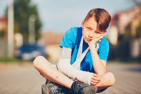 Photo for Mischievous boy with broken hand injured after accident during summer sports. - Royalty Free Image