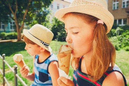 Photo for Summer day in the city. Cute siblings with hats eating big ice cream in the park. - Royalty Free Image