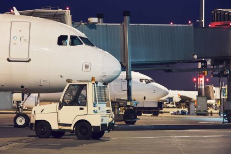 Photo for Busy airport at night. Preparation of the airplanes before flight. - Royalty Free Image