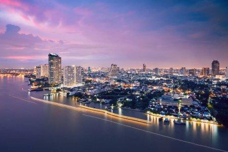 Photo pour Bangkok au crépuscule. Skyline de la ville avec trafic (bateaux en mouvement flou) sur la rivière Chao Phraya . - image libre de droit