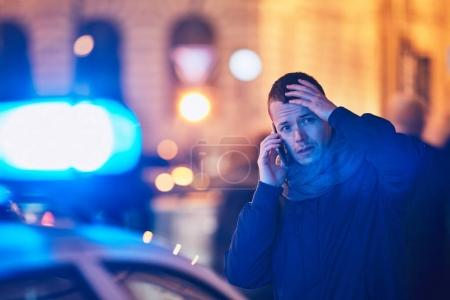 Photo for Young man calling after a crisis situation on city street. Themes crime, emergency medical service, fear or help. - Royalty Free Image